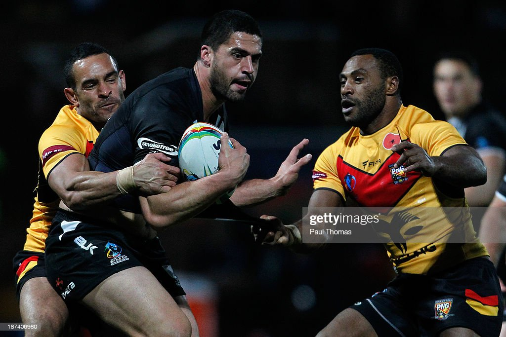 Jesse Bromwich (C) of New Zealand is tackled by Nene McDonald (L) and Dion Aiye of Papua New Guinea during the Rugby League World Cup Group B match at Headingley Stadium on November 8, 2013 in Leeds, England.
