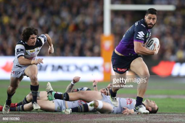Jesse Bromwich of the Storm breaks through Cowboys tackles as Shaun Fensom of the Cowboys is injured during the 2017 NRL Grand Final match between...