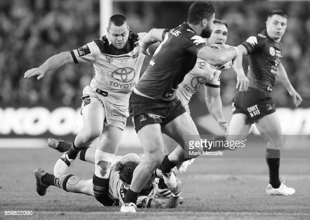 Jesse Bromwich of the Storm breaks through Cowboys tackles as Shaun Fensom of the Cowboys breaks his leg during the 2017 NRL Grand Final match...