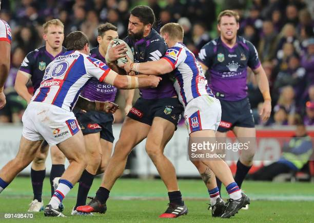 Jesse Bromwich of the Storm is tackled during the round 13 NRL match between the Melbourne Storm and the Newcastle Knights at AAMI Park on June 2...