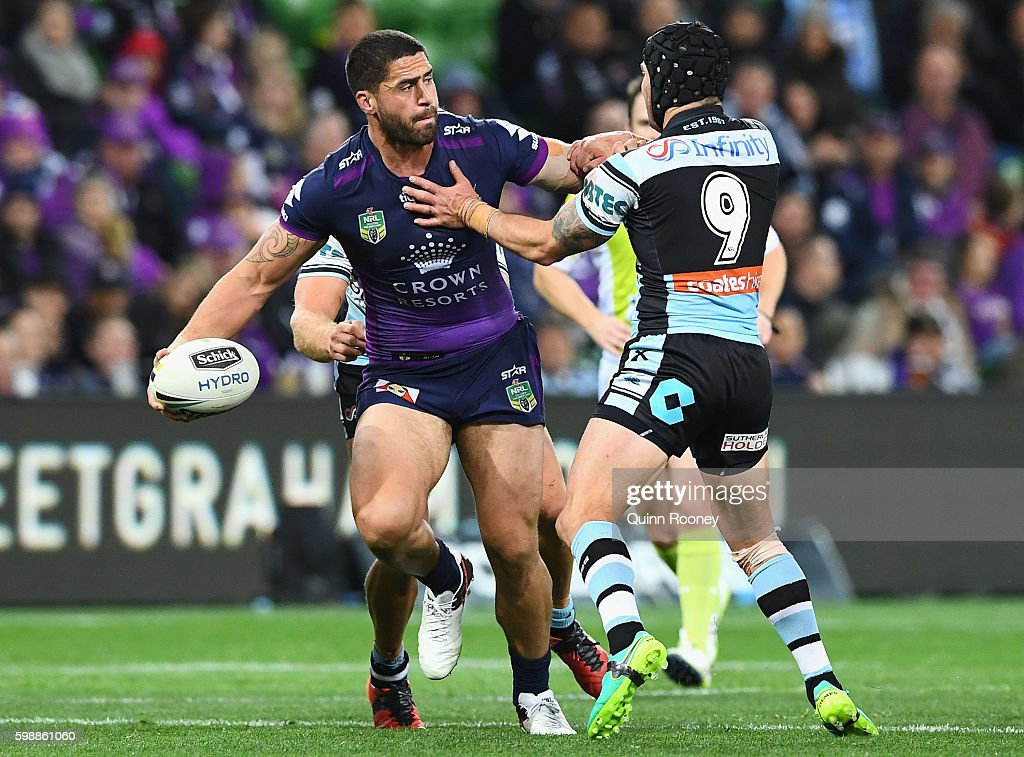 Jesse Bromwich of the Storm passes the ball whilst being tackled by Michael Ennis of the Sharks during the round 26 NRL match between the Melbourne Storm and the Cronulla Sharks at AAMI Park on September 3, 2016 in Melbourne, Australia.
