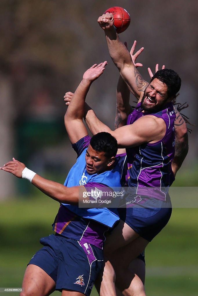 Jesse Bromwich punches an AFL football away from Richard Kennar during a Melbourne Storm NRL training session at Gosch's Paddock on August 22, 2014 in Melbourne, Australia.