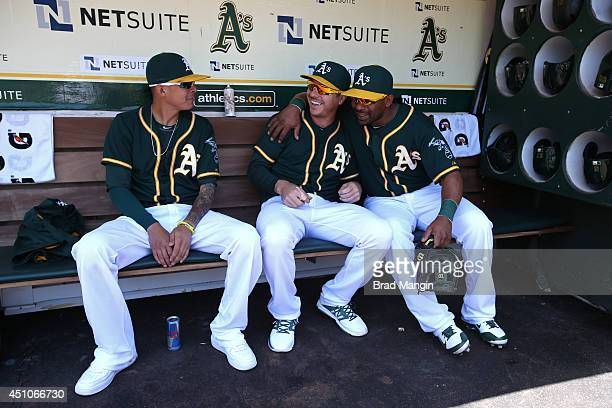 Jesse Chavez Scott Kazmir and Alberto Callaspo of the Oakland Athletics get ready in the dugout before the game against the Boston Red Sox at Oco...