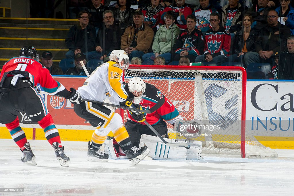 Jesse Gabrielle #12 of Brandon Wheat Kings takes a shot on Jackson Whistle #1 of Kelowna Rockets as he is checked by Madison Bowey #4 of Kelowna Rockets resulting in a penalty shot during the first period on October 25, 2014 at Prospera Place in Kelowna, British Columbia, Canada.