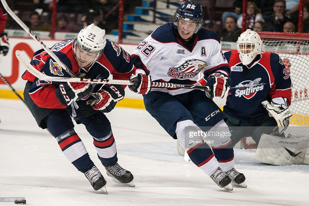 Jesse Graham #22 of the Saginaw Spirit battles for the puck against Sam Povorozniouk #22 of the Windsor Spitfires on March 6, 2014 at the WFCU Centre in Windsor, Ontario, Canada.