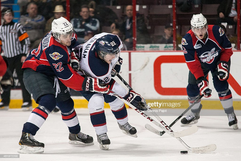 Jesse Graham #22 of the Saginaw Spirit moves the puck against Sam Povorozniouk #22 of the Windsor Spitfires on March 6, 2014 at the WFCU Centre in Windsor, Ontario, Canada.