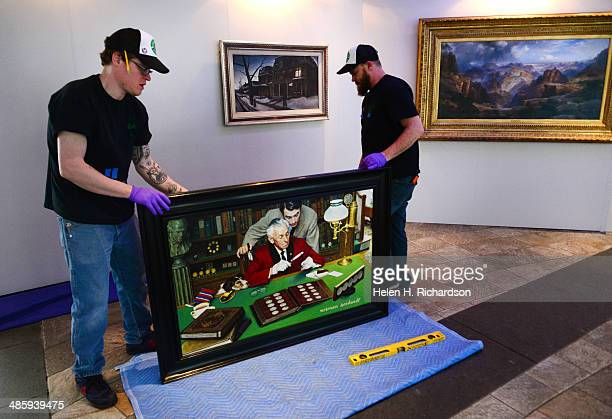Jesse Gregory left and Zach Smith right art handlers with Ship Art carefully lift up a painting by Norman Rockwell entitled The Collector to hang on...