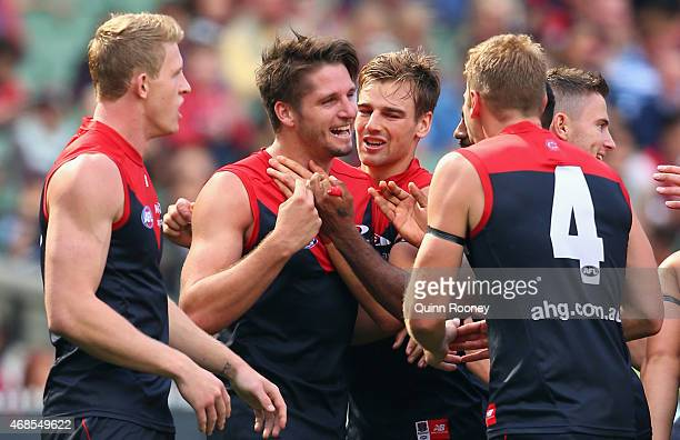 Jesse Hogan of the Demons is congratulated by team mates after kicking a goal during the round one AFL match between the Melbourne Demons and the...