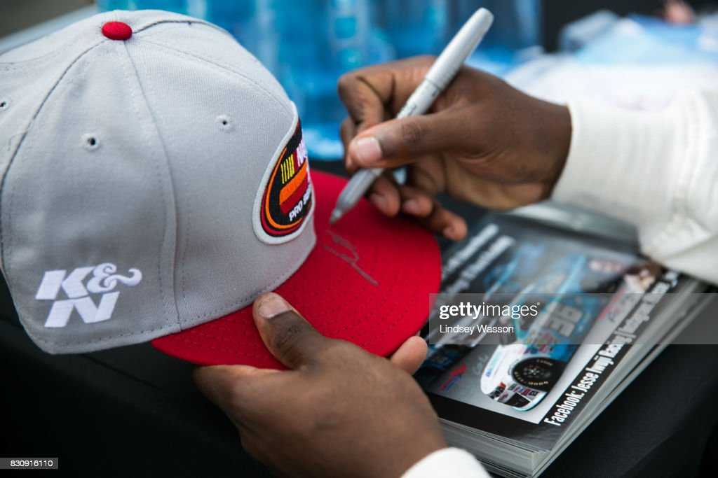 Jesse Iwuji #36 signs a fan's hat before the NASCAR K&N Pro Series West NAPA Auto Parts 150 on August 12, 2017 at Evergreen Speedway in Monroe, Washington.