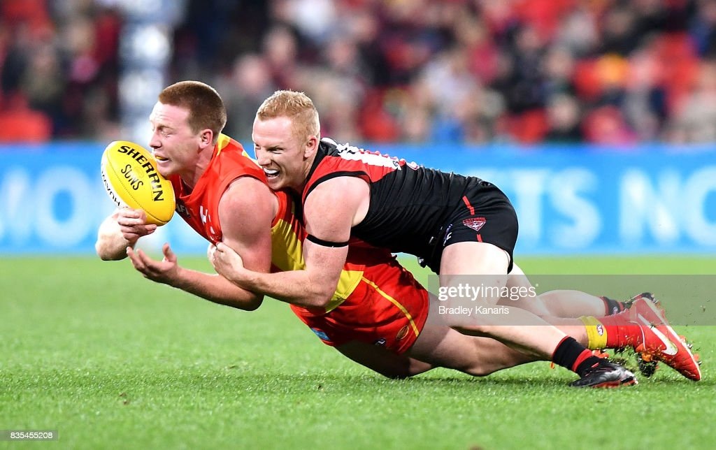 Jesse Joyce of the Suns is tackled by Josh Green of the Bombers during the round 22 AFL match between the Gold Coast Suns and the Essendon Bombers at Metricon Stadium on August 19, 2017 in Gold Coast, Australia.