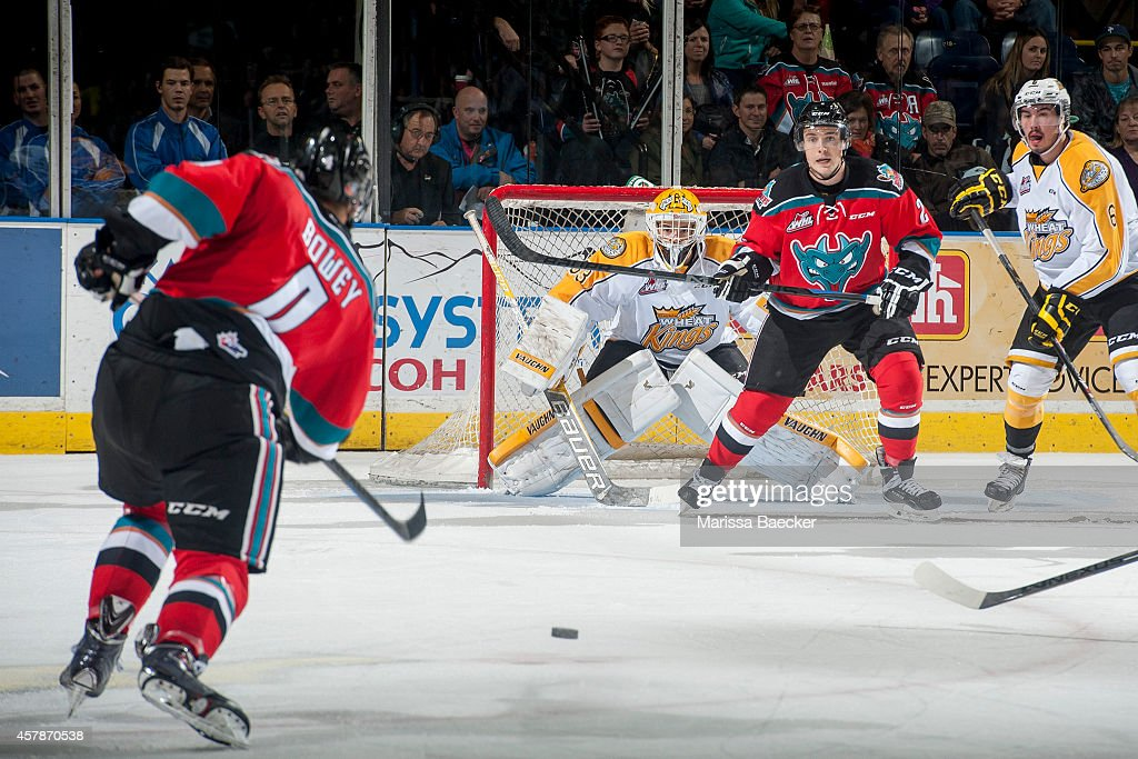 Jesse Lees #2 stands in front of the net as Madison Bowey #4 of Kelowna Rockets takes a shot on the net of Jordan Papirny #33 of Brandon Wheat Kings during the third period on October 25, 2014 at Prospera Place in Kelowna, British Columbia, Canada.