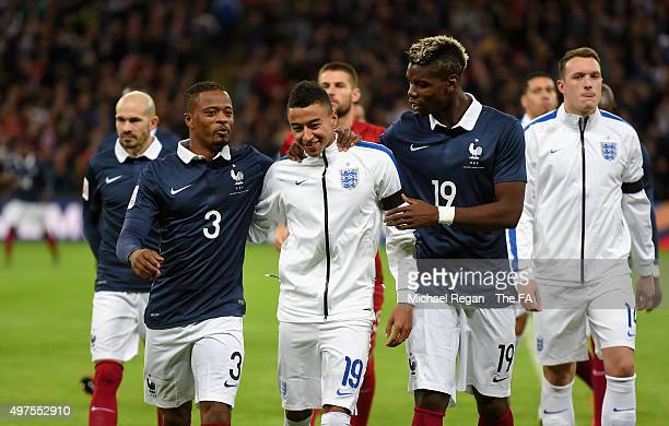 Jesse Lingard of England is greated by Patrice Evra of France and Paul Pogba of France prior to the International Friendly match between England and...