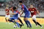 Jesse Lingard of Manchester United challenges with Gu Bin of Shanghai Shenhua during the Friendly Match between Shanghai Shenhua and Manchester...