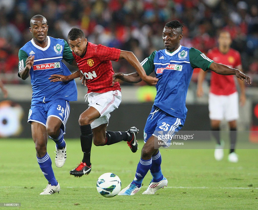 Jesse Lingard of Manchester United clashes with Ramson Zhuwawo (L) and Bukasa Kasonga of AmaZulu FC during the pre-season friendly between AmaZulu FC and Manchester United at Moses Mabhida Stadium on July 18, 2012 in Durban, South Africa.