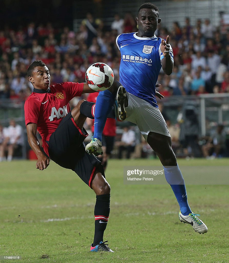 Jesse Lingard of Manchester United in action with Alex Akande of Kitchee FC during the pre-season friendly match between Kitchee FC and Manchester United as part of their pre-season tour of Bangkok, Australia, Japan and Hong Kong at Hong Kong Stadium on July 29, 2013 in So Kon Po, Hong Kong.