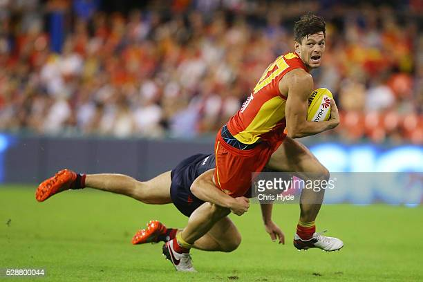 Jesse Lonergan of the Suns is tackled by Jack Viney of the Demons during the round seven AFL match between the Gold Coast Suns and the Melbourne...