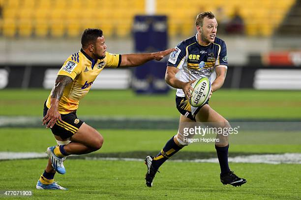 Jesse Mogg of the Brumbies evades the defence of Alapati Leiua of the Hurricanes during the round four Super Rugby match between the Hurricanes and...