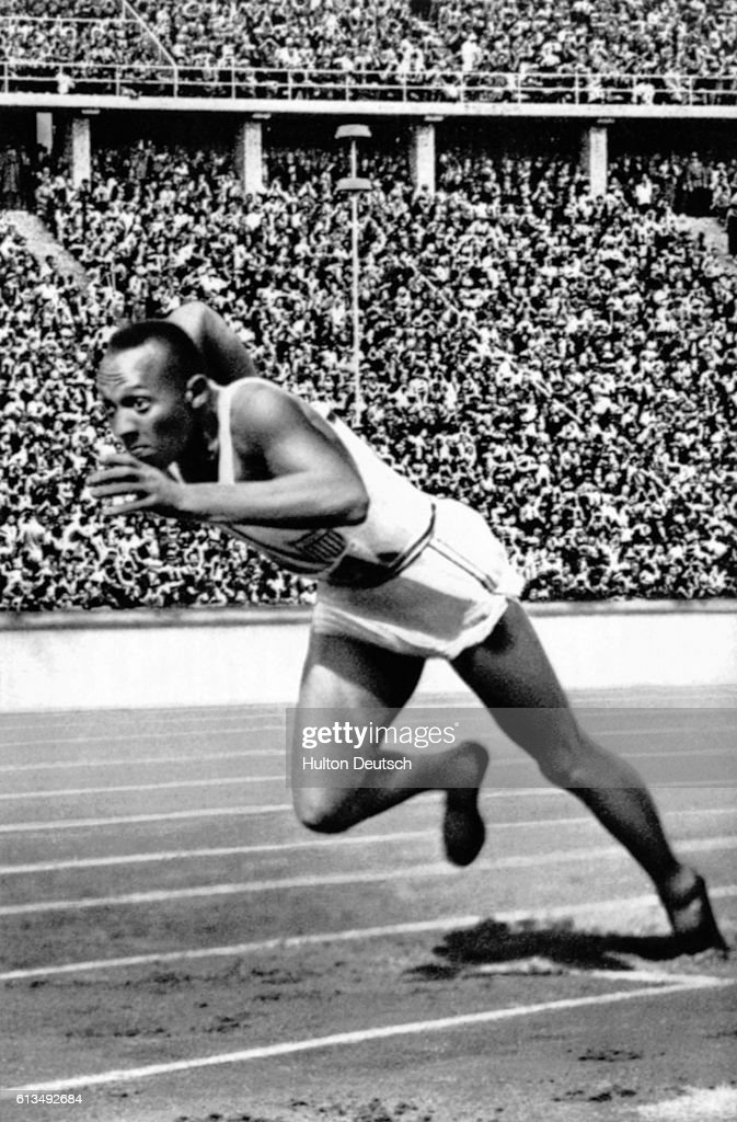 Jesse Owens leaps from the starting line during the 1936 Olympic Games in Berlin, with a crowd watching from the grandstand.