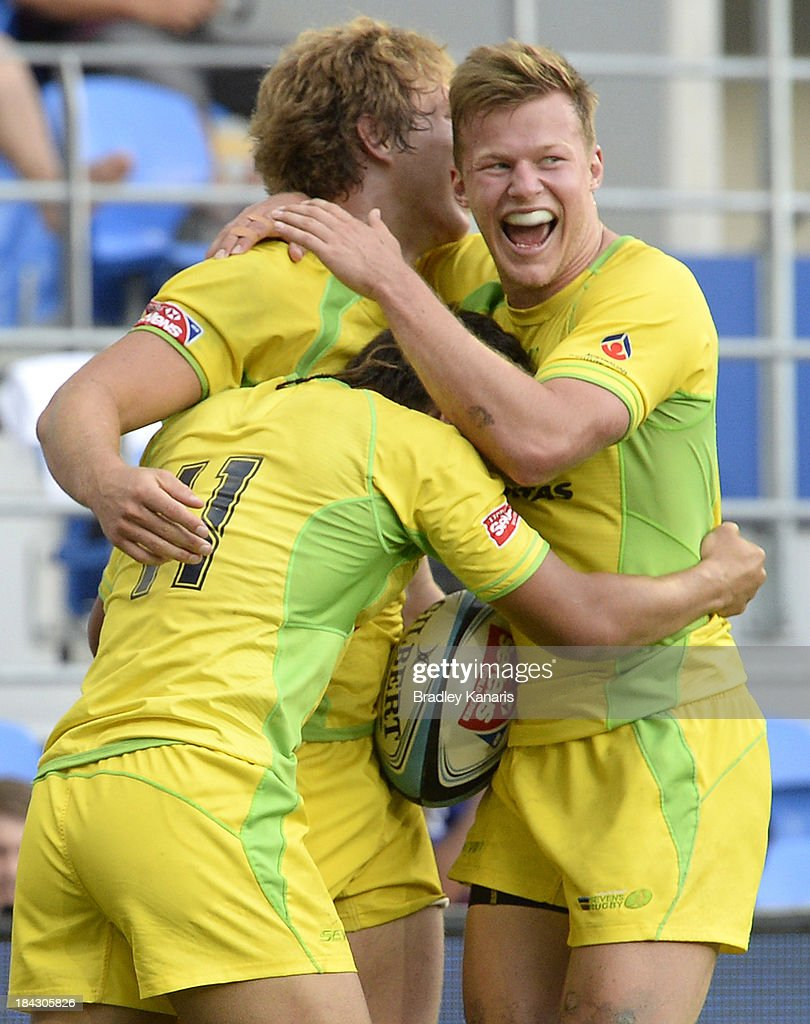 Jesse Parahi of Australia celebrates victory with team mates after scoring a try in extra time during the Gold Coast Sevens Cup semi final match between Australia and South Africa at Skilled Stadium on October 13, 2013 on the Gold Coast.