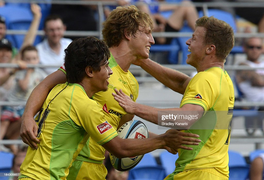 Jesse Parahi of Australia celebrates with team mates after scoring the match winning try in extra time during the Gold Coast Sevens semi final match between Australia and South Africa at Skilled Stadium on October 13, 2013 on the Gold Coast.