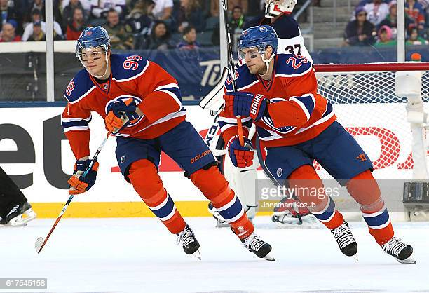 Jesse Puljujarvi and Leon Draisaitl of the Edmonton Oilers follow the play up the ice during first period action against the Winnipeg Jets in the...