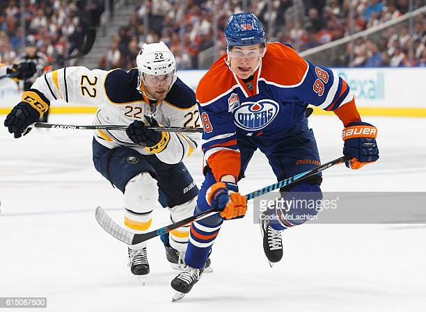 Jesse Puljujarvi of the Edmonton Oilers is pursued by Johan Larsson of the Buffalo Sabres on October 16 2016 at Rogers Place in Edmonton Alberta...