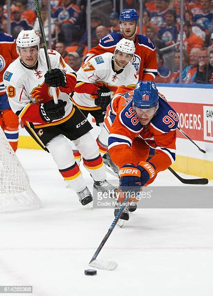 Jesse Puljujarvi of the Edmonton Oilers is pursued by Micheal Ferland and Michael Frolik of the Calgary Flames on October 12 2016 at Rogers Place in...