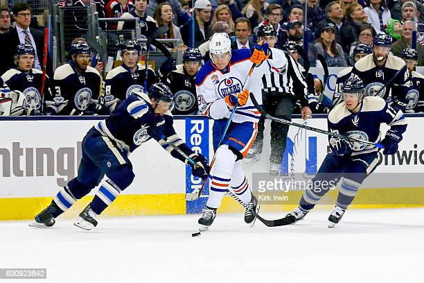 Jesse Puljujarvi of the Edmonton Oilers skates the puck through the defense of Jack Johnson of the Columbus Blue Jackets and Cam Atkinson of the...