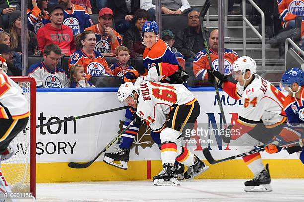 Jesse Puljujarvi of the Edmonton Oilers takes a hit from Brett Kulak of the Calgary Flames on September 26 2016 at Rogers Place in Edmonton Alberta...