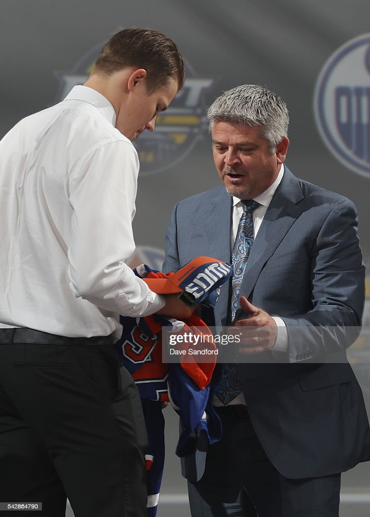 Jesse Puljujarvi puts on his jersey after being selected fourth overall by the Edmonton Oilers as head coach <a gi-track='captionPersonalityLinkClicked' href=/galleries/search?phrase=Todd+McLellan&family=editorial&specificpeople=543235 ng-click='$event.stopPropagation()'>Todd McLellan</a> looks on onstage during round one of the 2016 NHL Draft at First Niagara Center on June 24, 2016 in Buffalo, New York.