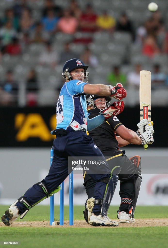 Jesse Ryder of Wellington bats as wicket keeper Gareth Hopkins of Auckland looks on during the HRV Cup Twenty20 match between the Auckland Aces and Wellington Firebirds at Eden Park on December 28, 2012 in Auckland, New Zealand.
