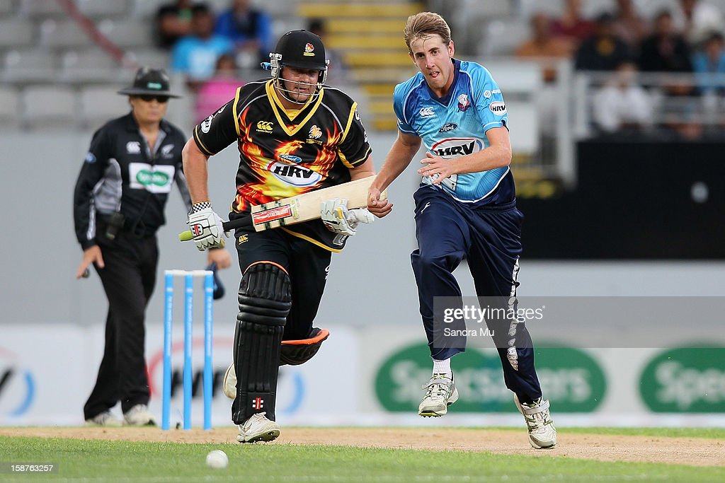 Jesse Ryder of Wellington makes a run as bowler Matt Quinn of Auckland chases the ball during the HRV Cup Twenty20 match between the Auckland Aces and Wellington Firebirds at Eden Park on December 28, 2012 in Auckland, New Zealand.