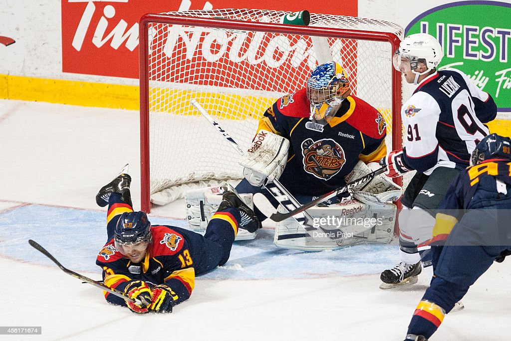 Jesse Saban #13 of the Erie Otters deflects a shot from Aaron Luchuk #91 of the Windsor Spitfires on September 26, 2014 at the WFCU Centre in Windsor, Ontario, Canada.