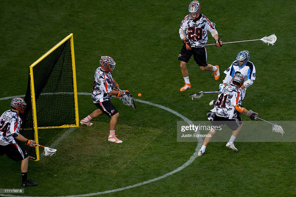 Jesse Schwartzman #19 of the Denver Outlaws makes a save against Steele Stanwick #6 of the Ohio Machine as Chris O'Dougherty #24, Lee Zink #29 and Dillon Roy #91 defend during the second quarter at Sports Authority Field at Mile High on June 22, 2013 in Denver, Colorado.