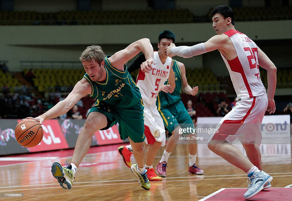 Jesse Wagstaff (L) of the Boomers brings the ball up the court with Ji Zhe of China during game three of the series between the Australian Boomers and China at Tianjin Sports Center on June 12, 2013 in Tianjin, China.