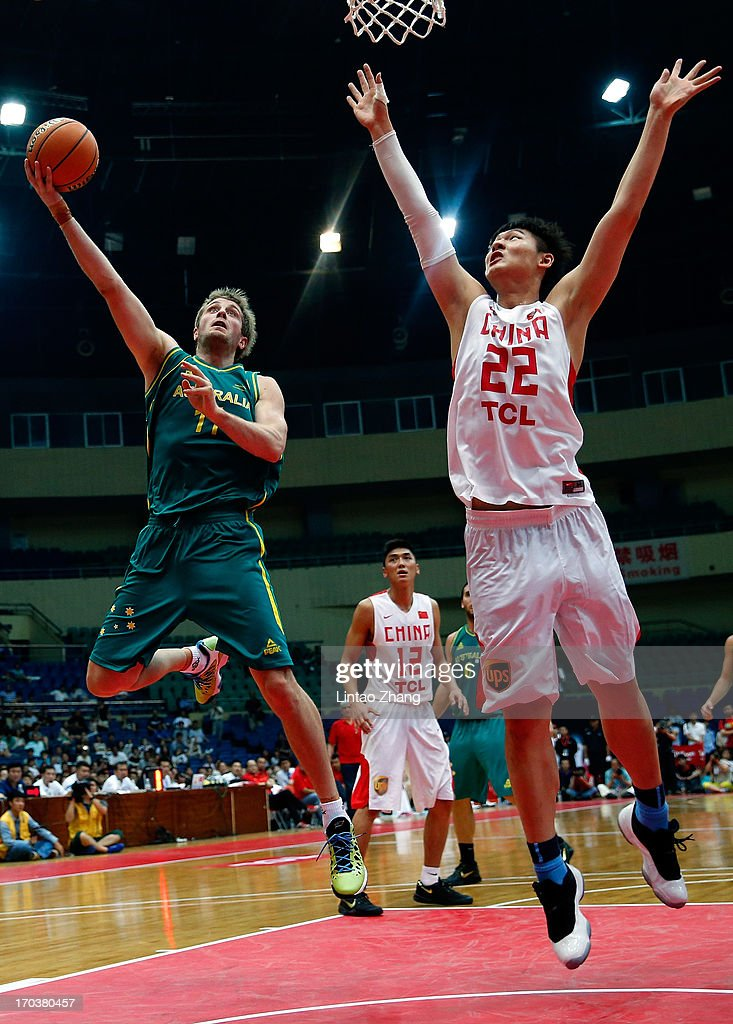 Jesse Wagstaff of the Boomers drives to the basket against Wang Zhelin of China (R) during game three of the series between the Australian Boomers and China at Tianjin Sports Center on June 12, 2013 in Tianjin, China.