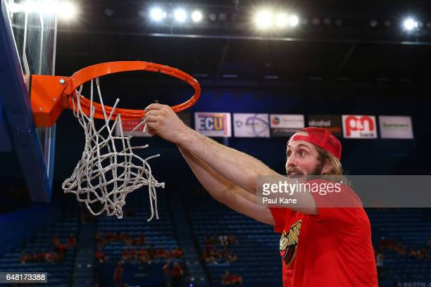 Jesse Wagstaff of the Wildcats cuts the net after winning game three and the NBL Grand Final series between the Perth Wildcats and the Illawarra...