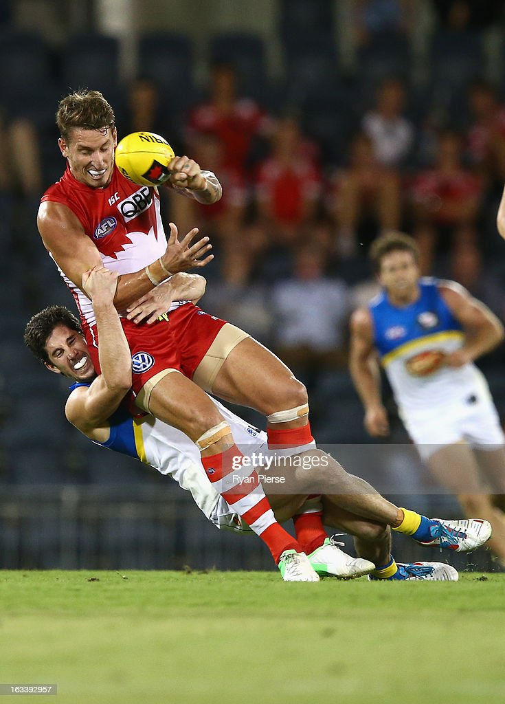 Jesse White of the Swans is tackled by Michael Rischitelli of the Suns during the round three NAB Cup AFL match between the Sydney Swans and the Gold Coast Suns at Blacktown International Sportspark on March 9, 2013 in Sydney, Australia.