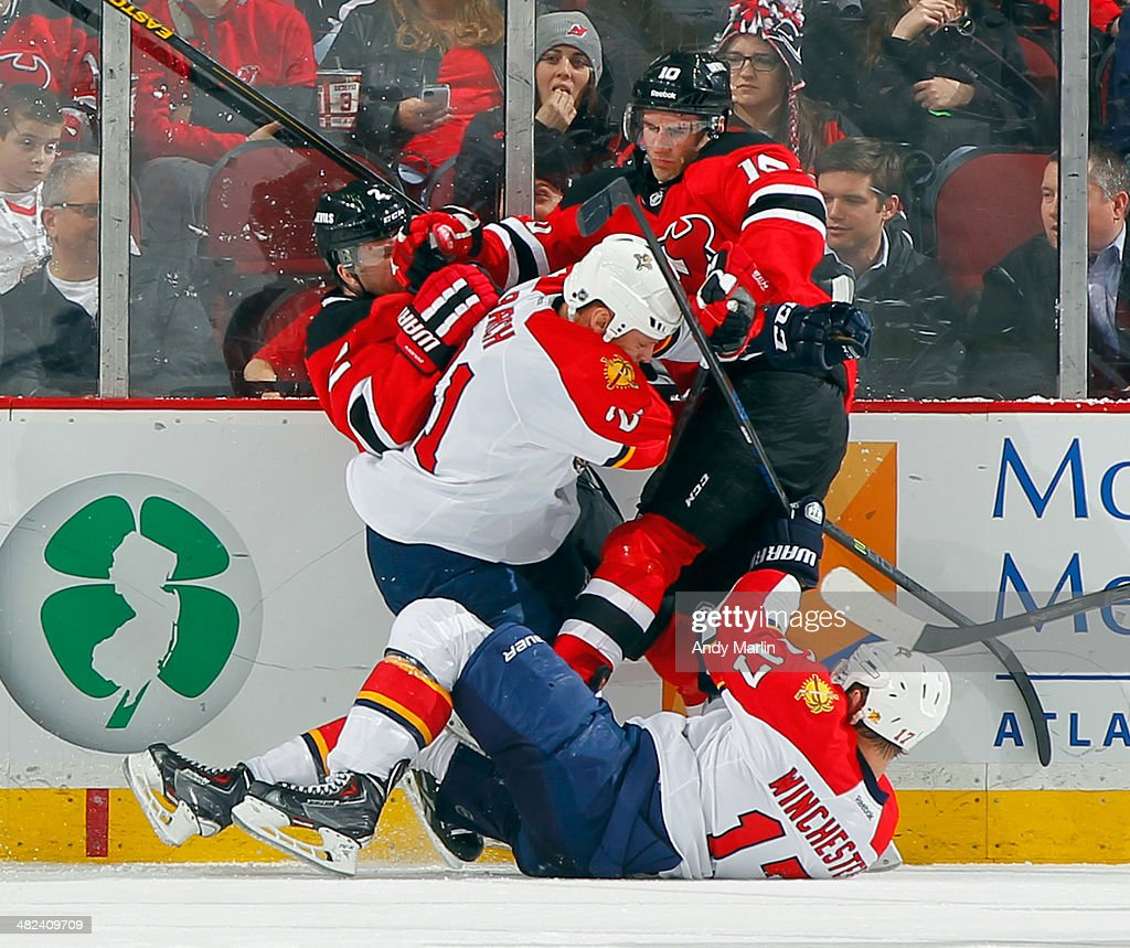 Jesse Winchester and Krys Barch of the Florida Panthers and Adam Henrique and Marek Zidlicky of the New Jersey Devils collide at the boards during...