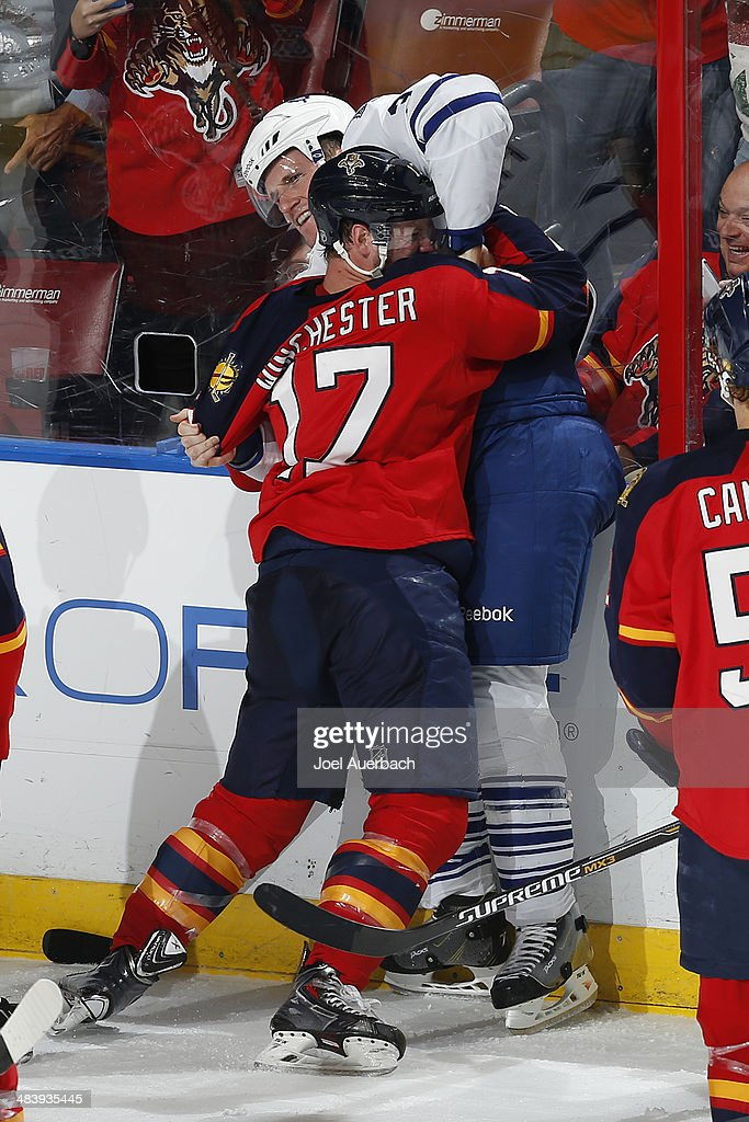 Jesse Winchester #17 of the Florida Panthers and <a gi-track='captionPersonalityLinkClicked' href=/galleries/search?phrase=Dion+Phaneuf&family=editorial&specificpeople=545455 ng-click='$event.stopPropagation()'>Dion Phaneuf</a> #3 of the Toronto Maple Leafs fight along the boards during third period action at the BB&T Center on April 10, 2014 in Sunrise, Florida. The Panthers defeated the Maple Leafs 4-2.