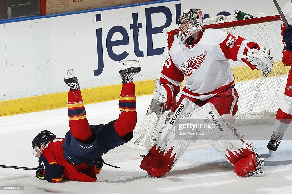 Jesse Winchester #17 of the Florida Panthers is upended by goaltender <a gi-track='captionPersonalityLinkClicked' href=/galleries/search?phrase=Jimmy+Howard&family=editorial&specificpeople=2118637 ng-click='$event.stopPropagation()'>Jimmy Howard</a> #35 of the Detroit Red Wings at the BB&T Center on December 10, 2013 in Sunrise, Florida. The Panthers defeated the Red Wings 3-2 in a shootout.
