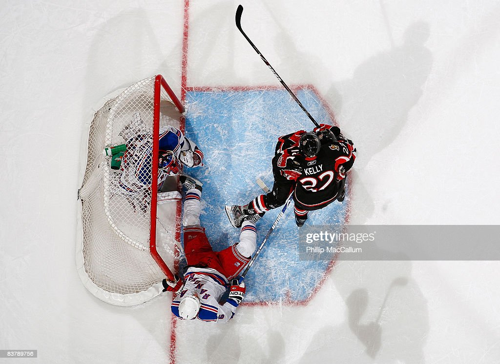 Jesse Winchester of the Ottawa Senators emerges from the net to celebrate his goal with teammate Chris Kelly while Steve Valiquette and Wade Redden...