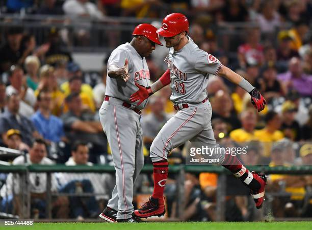 Jesse Winker celebrates his solo home run with Billy Hatcher of the Cincinnati Reds during the seventh inning against the Pittsburgh Pirates at PNC...