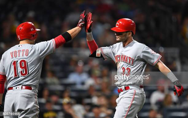 Jesse Winker celebrates his solo home run with Joey Votto of the Cincinnati Reds during the seventh inning against the Pittsburgh Pirates at PNC Park...