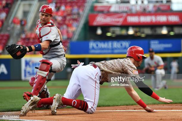 Jesse Winker of the Cincinnati Reds dives past catcher Carson Kelly of the St Louis Cardinals for a run in the first inning at Great American Ball...