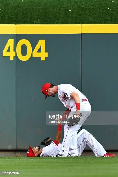 Jesse Winker of the Cincinnati Reds helps up Billy Hamilton of the Cincinnati Reds after Hamilton made a leaping catch off the center field wall in...
