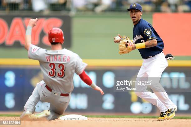 Jesse Winker of the Cincinnati Reds is forced out at second base as Orlando Arcia of the Milwaukee Brewers turns the double play during the seventh...