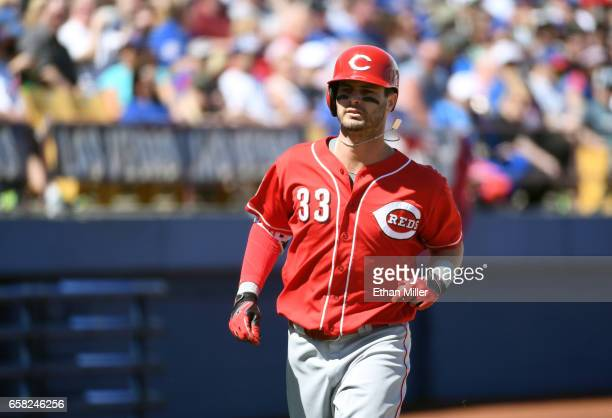 Jesse Winker of the Cincinnati Reds rounds the bases after hitting a home run against the Chicago Cubs in the second inning of their exhibition game...