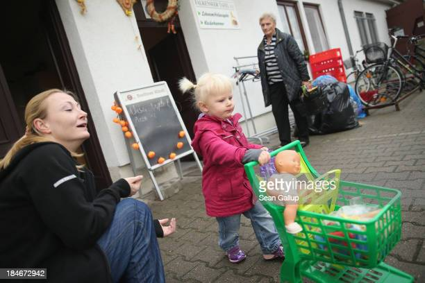 Jessica a mother of two and who only recently began coming to the food bank prepares to depart after buying groceries at the Falkenseer Tafel food...