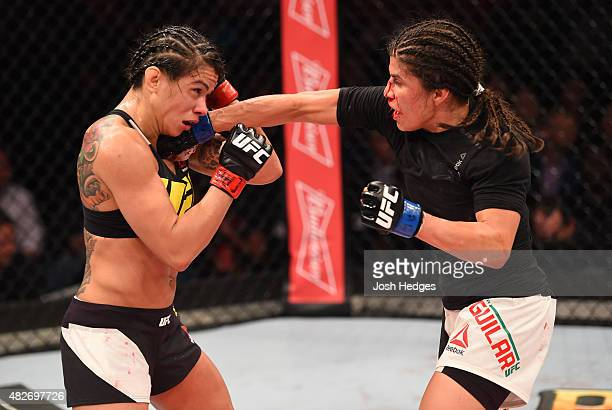 Jessica Aguilar of the United States punches Claudia Gadelha of Brazil in their women's strawweight bout during the UFC 190 event inside HSBC Arena...